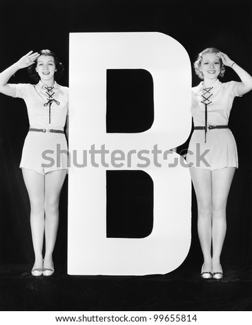 Two women saluting with huge letter B - stock photo
