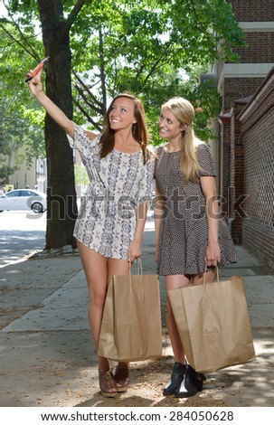 Two women shop together on city street - both carry brown paper shopping bags - taking a selfie (photo) with cell phone camera - stock photo