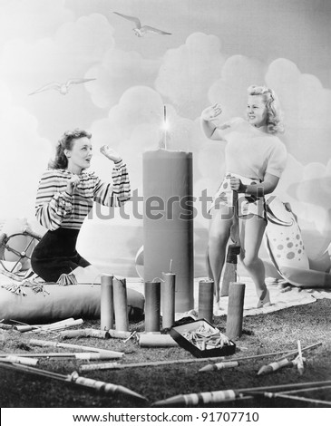 Two women sitting around fire works - stock photo