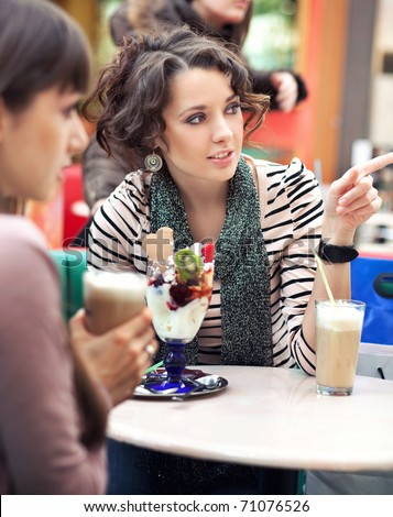 two women sitting in cafe and have a nice conversation - stock photo