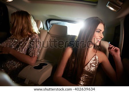 Two women sitting in limo look out of windows, in-car view - stock photo