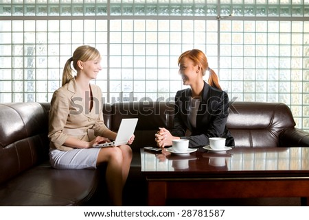 Two women sitting on couch and talking. One of them doing something on laptop.