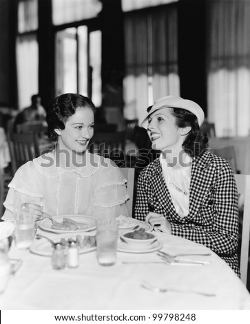 Two women sitting together in a restaurant - stock photo