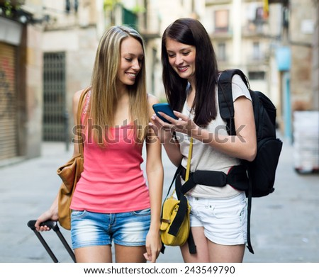 Two women smiling with luggage and using the map at smartphone - stock photo