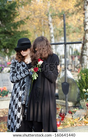 Two women standing above gravestone on autumn day - stock photo