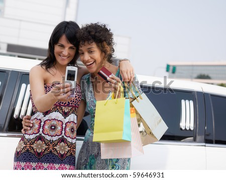 two women standing by limousine and taking picture on mobile phone. Horizontal shape, waist up, copy space - stock photo