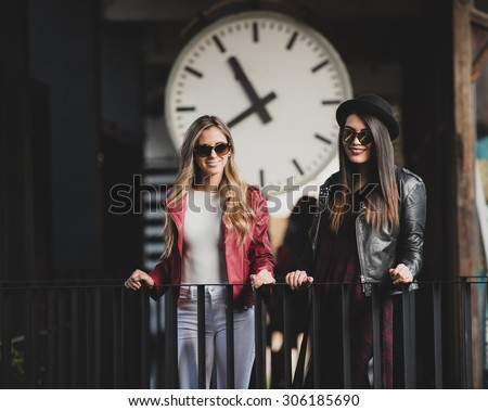 Two women standing in front of a big clock. Great urban and lifestyle shot. - stock photo