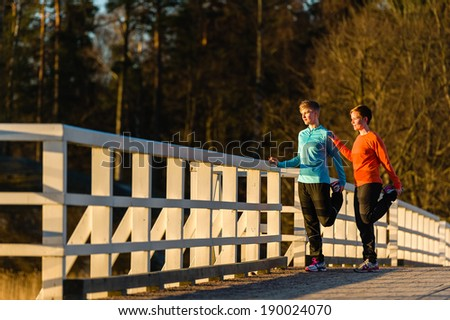 Two women stretch together on the bridge at sunrise - stock photo