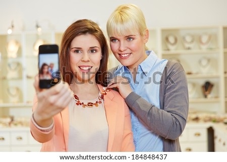 Two women taking a selfie while shopping in a jewelry store