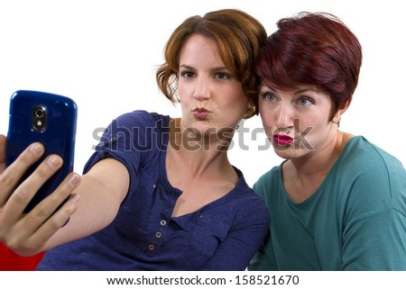 two women taking self portraits with a cell phone - stock photo