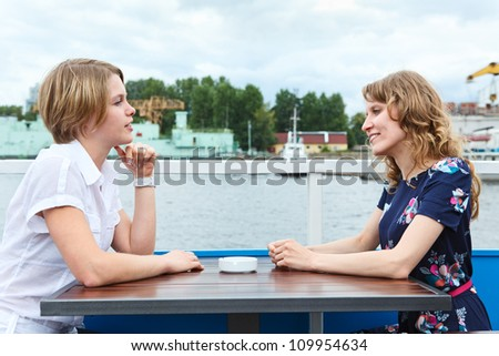 Two women talking each other at cafe table outdoors - stock photo