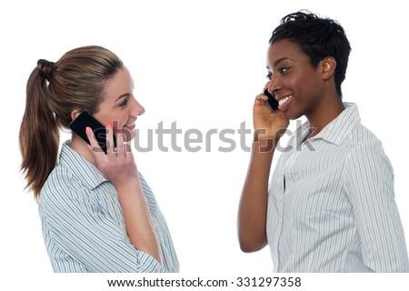 Two women talking on the phone, white background. - stock photo