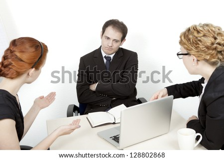 Two women try to explain a business proposal to an unimpressed man. Business meeting concept