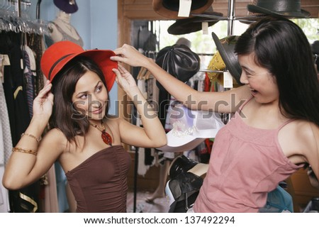 Two women trying on hats - stock photo