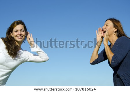 Two women, two generations, mother and daughter, two friends, communicating, one shouting, one listening, great distance, in front of a blurred green forest background - stock photo