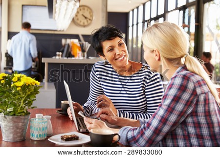 Two women using laptop computer in a coffee shop - stock photo