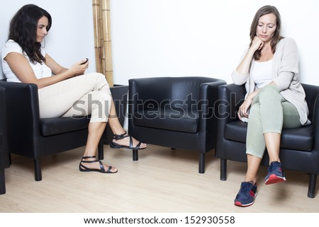 Two women waiting at doctor in waiting room - stock photo