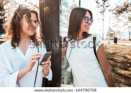 Two women waiting for a bus at a bus stop.Girls is standing on bus station.girl chatting,Girl wear stylish white shirt,attractive,pretty face,happy woman in sunglasses,travel mood,tan,hipster,laugh