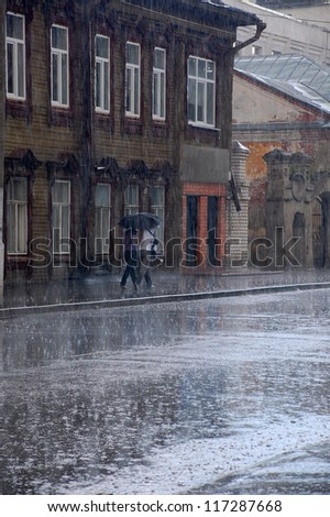 Two women walk in the rain down the street of the old Russian town - stock photo