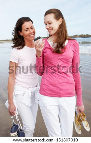 Two Women Walking Along Beach Looking At Mobile Phone