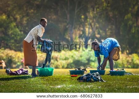 Two women washing clothes on the banks of Lake Naivasha National Park. 02. 01. 2006 Africa. Kenya.