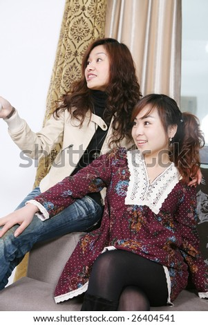 two women watch TV at home - stock photo