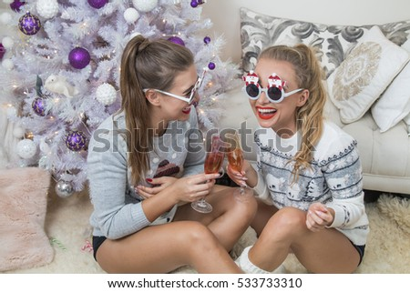 two women wearing christmas sunglasses and jumpers with champagne glasses