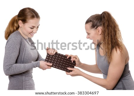 two women wearing fitness clothes fighting over chocolate