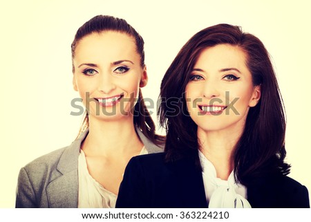 Two women wearing office outfits.
