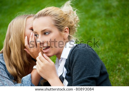 Two women whispering and smiling at the city park. Sitting on green grass - stock photo