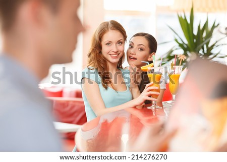 Two women whispering and smiling in cafe. redhead girl looking at boy at next table - stock photo