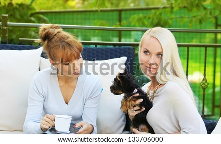Two women with a dog - stock photo