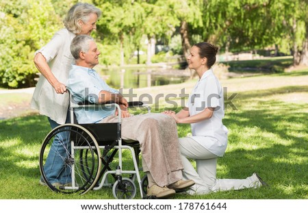 Two women with a mature man sitting in wheel chair at the park - stock photo