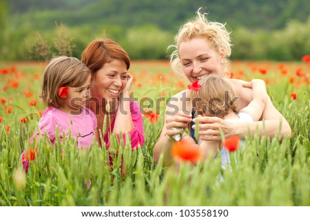 Two women with children in poppy field