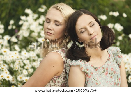Two women with closing eyes sitting on the grass