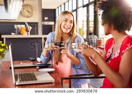 Two women with computer laughing in a coffee shop - stock photo