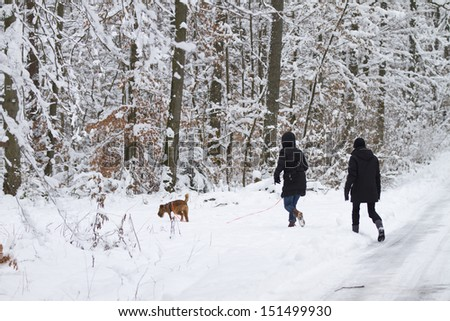 two women with dog in winter - stock photo