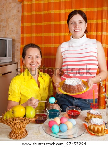 Two women with  Easter cake and eggs in home - stock photo