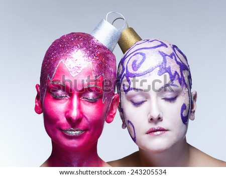 Two women with fantastic makeup posing as Christmas ornaments - stock photo