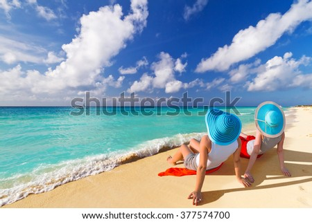 Two women with hats enjoying sun holidays on the tropical beach