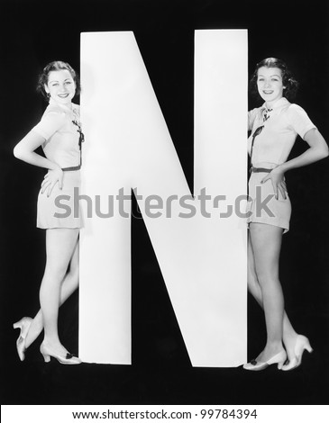 Two women with huge letter N - stock photo