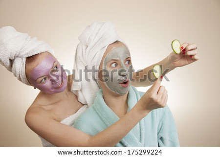 two women with masks applied on their faces looking at slices of cucumbers - stock photo