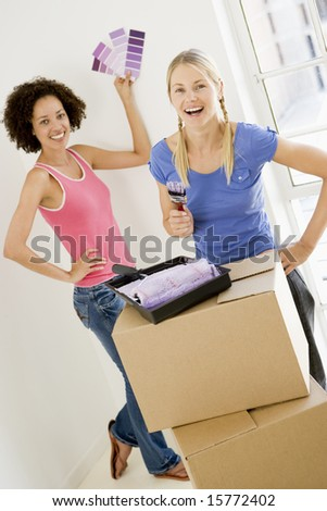 Two women with paint swatches in new home smiling - stock photo
