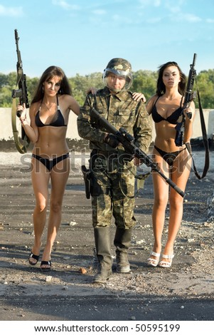 Two women with rifles leaning on soldier - stock photo