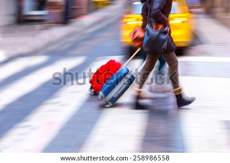 Two women with suitcases crossing street on zebra crossing - stock photo