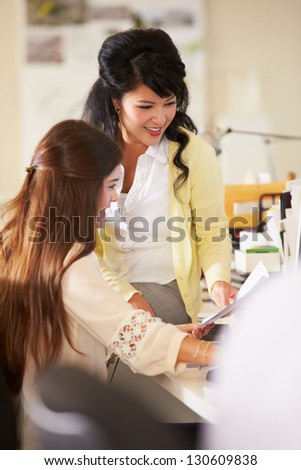 Two Women Working At Desks In Busy Creative Office - stock photo