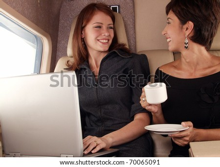 Two women working inside a private jet. - stock photo