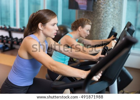 Two Women Working out Hard on Bikes in Gym