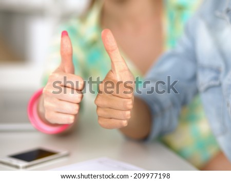 Two women working together at office, sitting on the desk and showing ok - stock photo