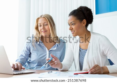 Two women working together in office - stock photo